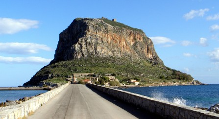 The Island of Monemvasia Monemvasia (Greek: Μονεμβασία) is a town and a municipality in Laconia, Greece. The town is located on a small island off the east coast of the Peloponnese.